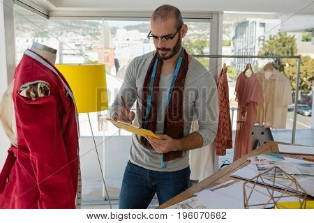 Designer writing on paper while standing by mannequin in studio