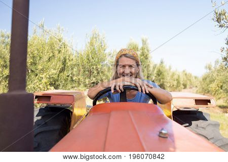 Portrait of happy woman sitting in tractor on a sunny day