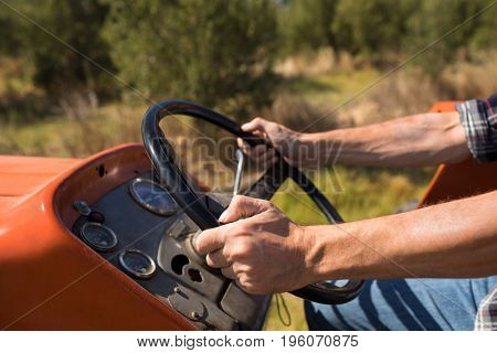 Mid section of man driving tractor in olive farm on a sunny day