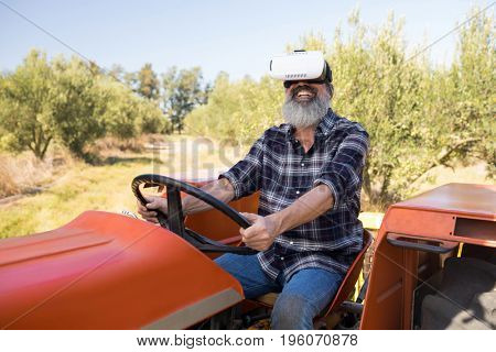 Happy man using virtual reality headset in tractor on a sunny day