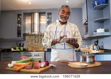 Portrait of smiling man using tablet computer while cooking food in kitchen at home