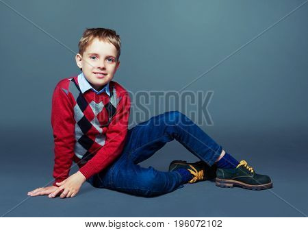 happy child wearing a sweater and jeans, isolated against grey background