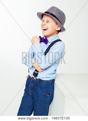 happy laughing child wearing a shirt and hat isolated against white background