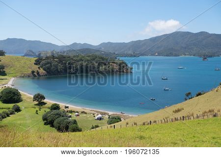 View of camping tents and anchored boats in summer from Urupukapuka Island in Bay of Islands New Zealand NZ