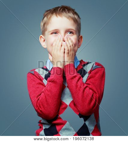 happy excited child cllosing his face and wearing a sweater  isolated against grey background