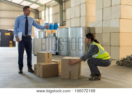 Manager instructing female worker while working in factory