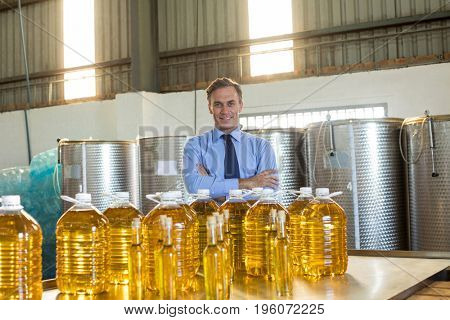 Portrait of manager standing with arms crossed in oil factory