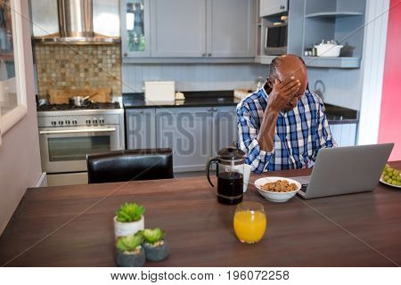 Senior man with head in hand using laptop while sitting at table in kitchen