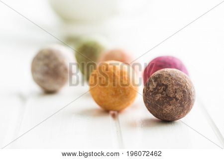 Sweet truffle balls on white table.