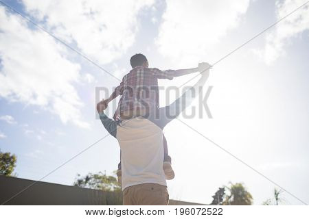 Rear view of father carrying son on shoulder while standing in yard against sky
