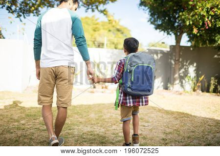 Rear view of father holding hand of son with backpack while walking in yard