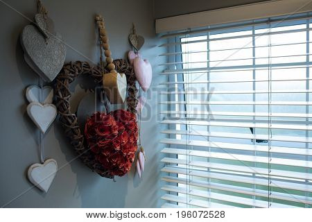 Close up of heart shape decoration hanging on wall by window at home