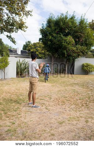 Father applauding while son cycling on field in yard