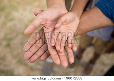 High angle view of family stacking hands while standing in yard