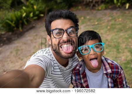 High angle view of father and son wearing sunglasses while sticking out tongue