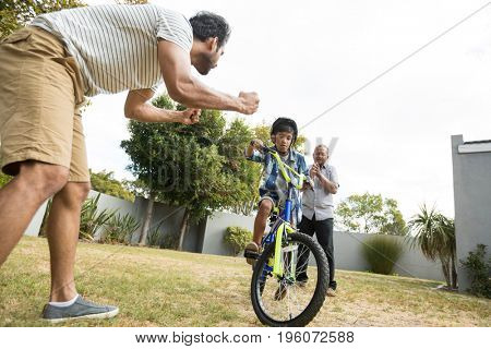 Father and grandfather cheering for boy cycling on field in yard