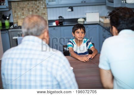 High angle view of father and grandfather talking to boy sitting by table at home