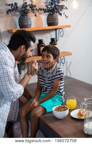 Father feeding cereal breakfast to son sitting on table at home