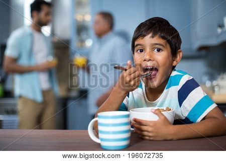 Portrait of boy having cereal breakfast with family in background at home