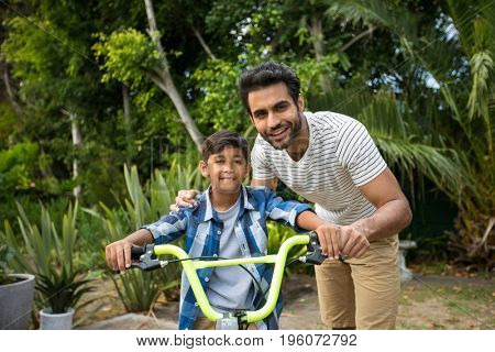 Portrait of father with son sitting on bicycle in yard
