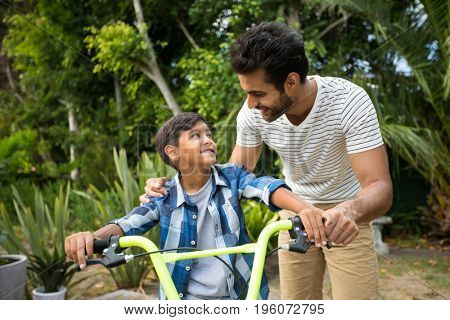 Father and son standing in yard with bicycle while looking at each other