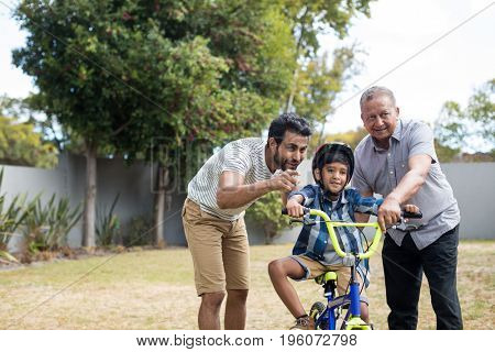 Boy learning bicycle with father and grandfather in yard