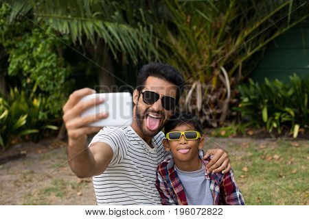 Playful father and son wearing sunglases while taking selfie