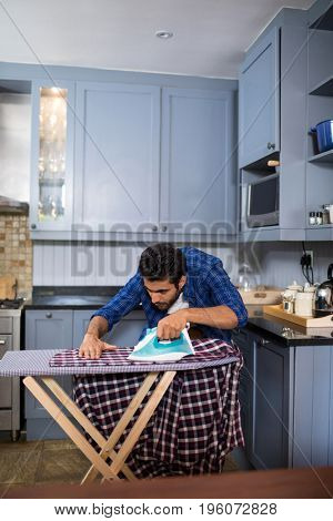 Man ironing shirt on board while standing in kitchen