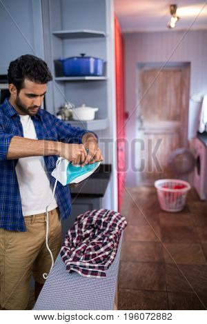 Young man adjusting iron during ironing shirt