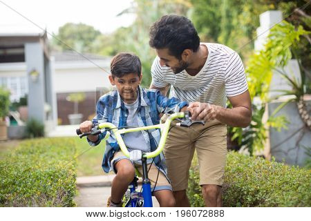 Man assisting son for cycling in yard