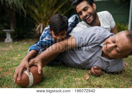 Happy family playing american football on field in yard