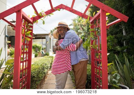 Side view of affectionate senior couple embracing while standing by metallic structure in yard