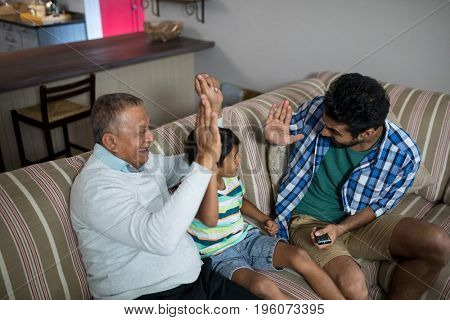 High angle view of family doing high five while sitting on sofa at home