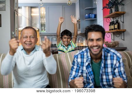 Happy family clenching fist while watching soccer match at home