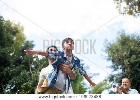Low angle view of man looking at father playing with son at park against sky