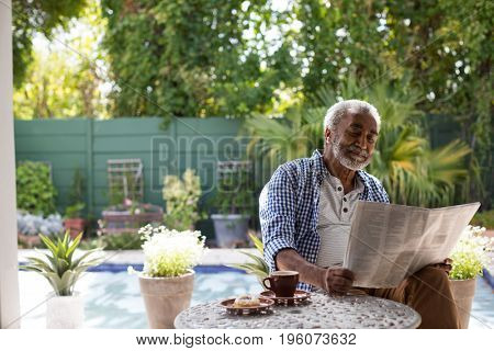 Senior man reading newspaper while sitting at table in yard