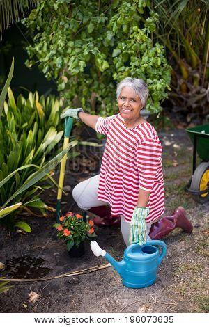 Portrait of woman kneeling on field while gardening in yard