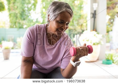Close up of senior woman exercising with dumbbell while sitting in yard