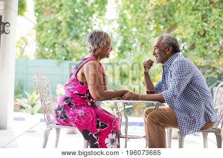 Happy senior couple talking while sitting at table in yard