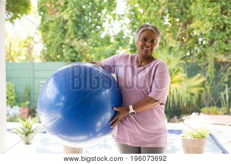 Portrait of woman holding exercise ball while standing in yard