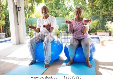 Portrait of senior couple lifting dumbbells while sitting on fitness ball in yard