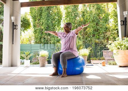 Senior woman with arms outstretched sitting on exercise ball under shed in yard