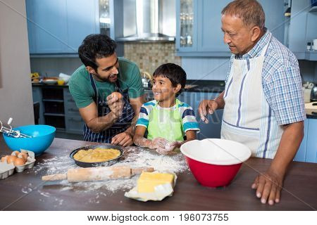 Man showing egg to boy standing by grandfather in kitchen at home
