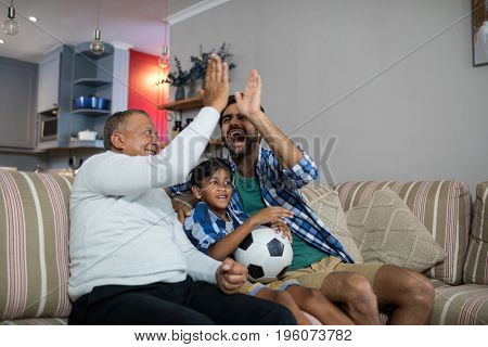 Happy family doing high five while watching soccer match at home