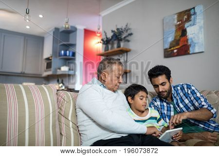 Father and grandfather pointing on tablet used by boy in living room at home