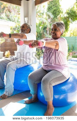 Full length of senior couple lifting dumbbells while sitting on fitness ball in yard