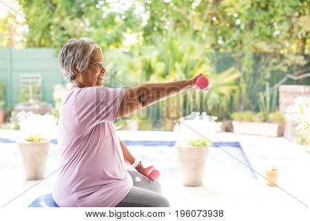 Side view of woman exercising with dumbbells while sitting on fitness ball in yard