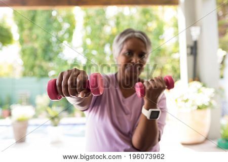 Portrait of senior smiling woman exercising with dumbbell while sitting in yard