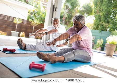 Full length of senior couple doing stretching exercise while sitting on exercise mat in yard