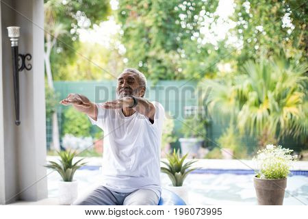 Senior man with arms outstretched exercising in yard
